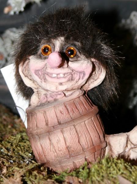 Kleiner Troll sitzt im Holzfass