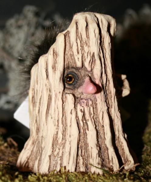 Troll lugt durch Astloch hinterm Baum